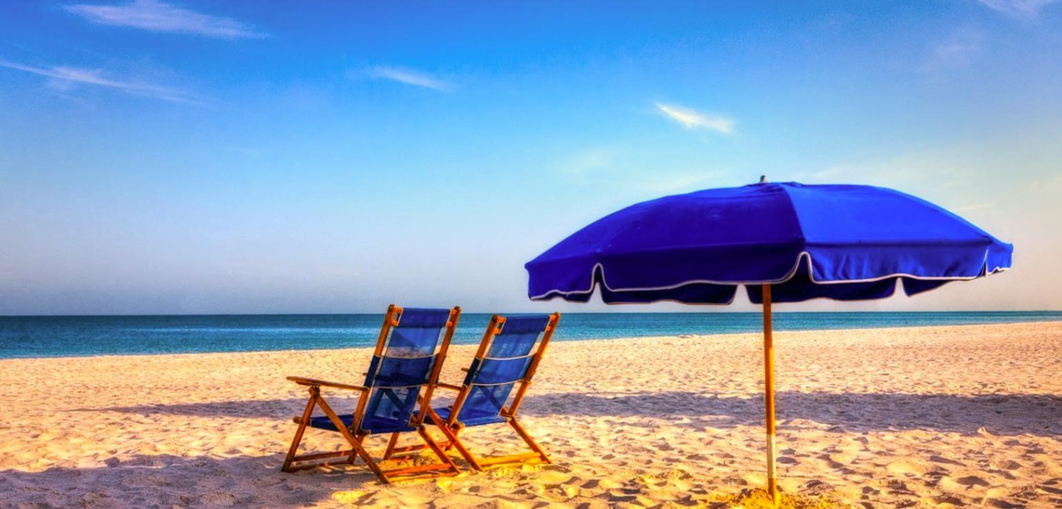 Beach with 2 chairs and a blue beach umbrella
